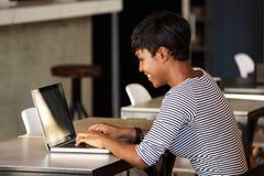 Le den unga kvinnan som använder bärbara datorn på kafét Arkivbilder