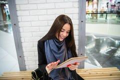 Le den unga kvinnan som använder den digitala minnestavlan på gallerian arkivfoton