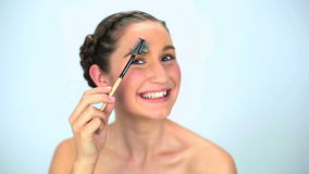 Le den unga kvinnan som borstar hennes ögonbryn lager videofilmer