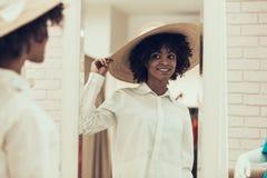 Le den unga kvinnan som försöker på Straw Hat i lager royaltyfri foto