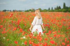 Le den unga kvinnan som går till och med det blommande fältet för röda blommor Royaltyfri Foto