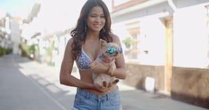 Le den unga kvinnan som kelar en liten hund stock video