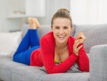Le den unga kvinnan som lägger på soffan i vardagsrum Arkivbilder