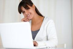 Le den unga kvinnan som ser dig som använder bärbara datorn Arkivbild