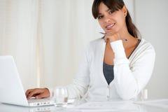 Le den unga kvinnan som ser dig som använder bärbara datorn Arkivbilder