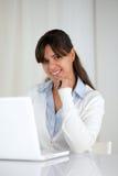 Le den unga kvinnan som ser dig som använder bärbara datorn Arkivfoto