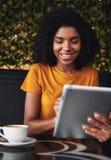 Le den unga kvinnan som sitter i kafé genom att använda den digitala minnestavlan royaltyfri foto
