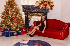Le den unga kvinnan som sitter på en röd soffa på jul royaltyfria foton