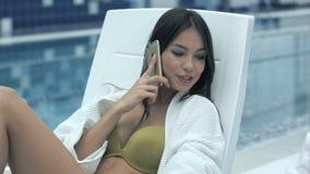 Le den unga kvinnan som talar på telefonen och pratar med hennes kvinnliga vänsammanträde på schäslonger nära pölen arkivfilmer