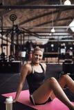 Le den unga kvinnan som tar ett avbrott från hennes idrottshallgenomkörare royaltyfri bild