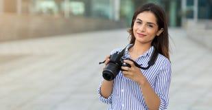 Le den unga kvinnan som utomhus rymmer kameran med kopieringsutrymme Fotograf turist royaltyfri foto