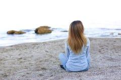 Le den unga kvinnan vilar på stranden och poserar in camera och att sitta Arkivfoto