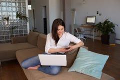 Le den unga kvinnliga bloggeren som avlägset arbetar på bärbara datorn och mobiltelefonen med internet Caucasian kvinnacopywriter royaltyfria bilder