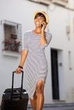 Le den unga kvinnliga handelsresanden som går med mobiltelefonen och resväskan Arkivfoton