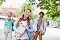 Le den unga kvinnliga studenten med vänner i bakgrund på gatan arkivbild