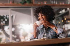 Le den unga kvinnlign som har kaffe i en restaurang royaltyfria foton