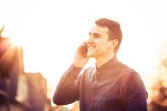 Le den unga mannen med mobiltelefonen som är utomhus- i solnedgång arkivbild