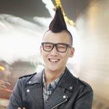 Le den unga mannen med punkrockMohawk och exponeringsglas som ser kameran fotografering för bildbyråer