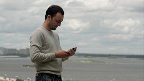 Le den unga mannen som använder en smartphone nära floden arkivfoto