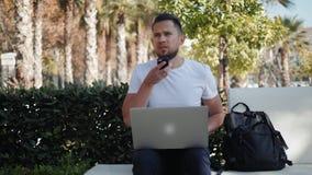 Le den unga mannen som arbetar på bärbara datorn som sitter i bänk med den loppfallet och påsen, turist- man för ryggsäck på seme arkivfilmer