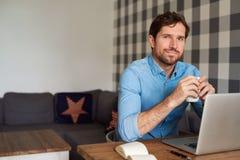 Le den unga mannen som direktanslutet dricker kaffe och arbete hemma Arkivbild