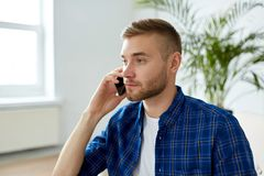 Le den unga mannen som kallar på smartphonen på kontoret Arkivfoto