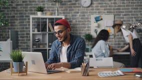 Le den unga mannen som skriver i anteckningsbok och arbetar med bärbara datorn i idérikt kontor arkivfilmer