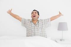 Le den unga mannen som sträcker hans armar i säng royaltyfria foton