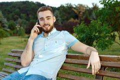 Le den unga mannen som talar på mobiltelefonen Royaltyfri Fotografi