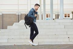 Le den unga mannen som utomhus går och talar på mobiltelefonen Royaltyfria Foton