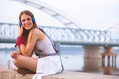 Le den unga stads- kvinnan som utomhus använder den smarta telefonen, medan vänta på hennes vänner royaltyfria bilder