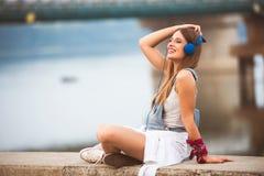 Le den unga stads- kvinnan som utomhus använder den smarta telefonen, medan vänta på hennes vänner fotografering för bildbyråer