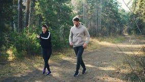 Le den ungdomarkvinnan och mannen hoppar i skogen som gör sportar som bär träningsoveraller och gymnastikskor som har gyckel och stock video