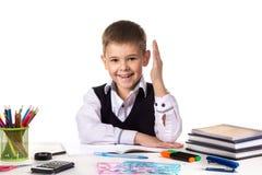 Le den utmärkta eleven med handen upp sammanträde på tabellen på den vita bakgrunden Arkivbilder