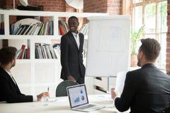 Le den vänliga afrikanska lagledaren som ger presentation till businessme royaltyfria bilder