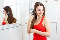 Le den varma flickan som kammar hennes hår i badrummet Arkivbilder