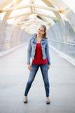 le den vita Caucasian flickakvinnan med ponnysvansen, bärande jeansomslag utanför i bro för gata för aftonnattstad arkivfoto