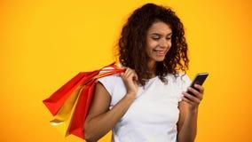 Le denamerikan kvinnan som rymmer shoppingp?sar och smartphonen, online-lager royaltyfri bild
