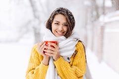 Le denhaired flickan i en gul tröja, rånar jeans och ett vitt halsdukanseende med ett rött på en snöig gata på a royaltyfria bilder