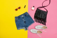 Le denim court-circuite, les espadrilles blanches, sac à main noir, lunettes de soleil lumineux Photo stock
