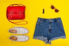 Le denim court-circuite, les espadrilles blanches, sac à main rouge Fond jaune lumineux concept à la mode Photo stock