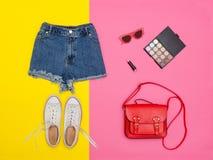 Le denim court-circuite, les espadrilles blanches, sac à main rouge Fond jaune lumineux concept à la mode Image stock