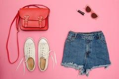 Le denim court-circuite, les espadrilles blanches, sac à main rouge Fond rose lumineux concept à la mode Photographie stock