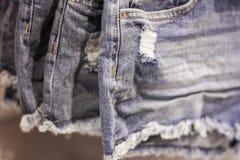 Le denim court-circuite sur un cintre dans un magasin d'habillement du ` s de femmes image libre de droits