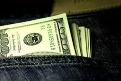 Le denominazioni in una denominazione di cento dollari in jeans intascano il primo piano Immagine Stock