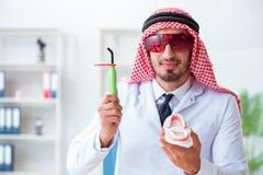 Le dentiste arabe travaillant au nouvel implant de dents image stock