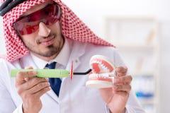 Le dentiste arabe travaillant au nouvel implant de dents photo stock