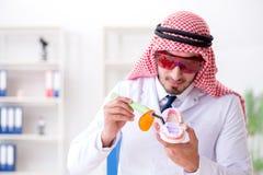 Le dentiste arabe travaillant au nouvel implant de dents image libre de droits