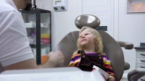 Le dentiste conduit un examen courant banque de vidéos