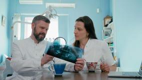 Le dentiste de deux médecins examinent la photographie de rayon X utilisant la loupe et l'ordinateur portable banque de vidéos
